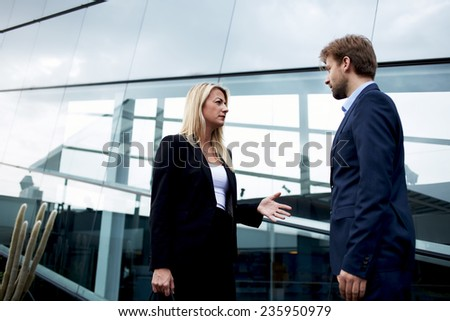 Attractive businesswoman talking with her business partner standing near skyscraper office, confident businesspeople having serious conversation about the work, angry boss discussing with employee