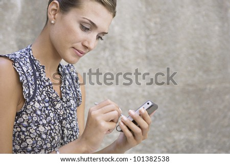 Attractive businesswoman using a digital organizer outdoors.