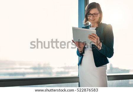 Attractive businesswoman using a digital tablet while standing in front of windows in an office building overlooking the city stock photo