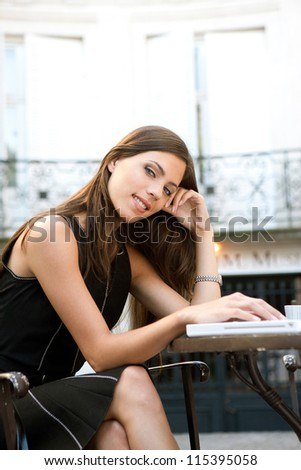 Attractive businesswoman using a laptop computer while sitting in a coffee shop, outdoors.