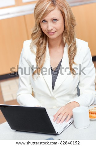 Attractive businesswoman using her laptop with a mug and food in her office at work