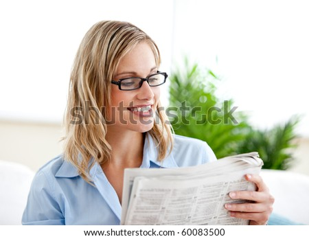 Attractive businesswoman wearing glasses and reading the newspaper sitting on the sofa at home - stock photo