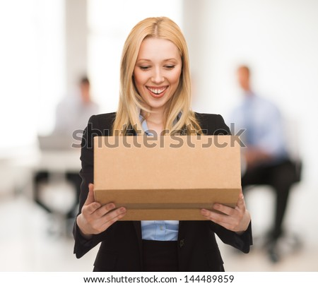 attractive businesswoman with cardboard box in office