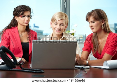 Attractive businesswomen sitting at table in meeting room, using laptop computer, smiling.