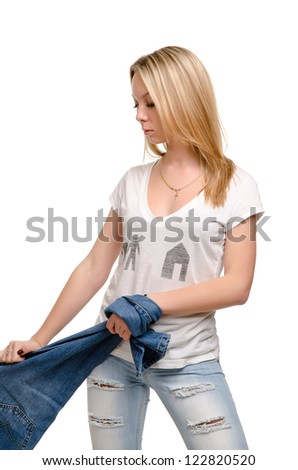 Attractive casual blonde girl with a lovely figure standing pulling a pair of blue denim jeans, studio portrait isolated on white