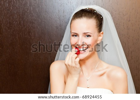 attractive caucasian bride eating strawberry and looking at camera