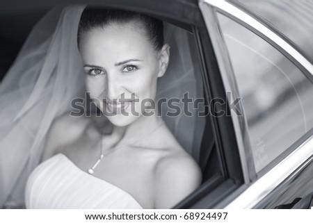 attractive caucasian bride in car smile to the camera - stock photo
