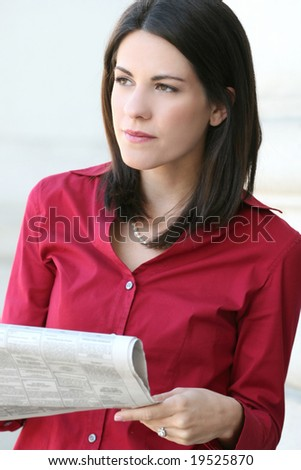 Attractive Caucasian business woman reading a newspaper. Suitable for a variety of economic and political themes