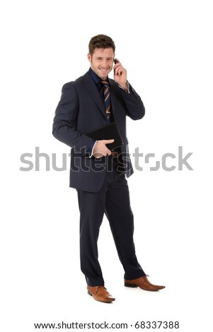 Attractive caucasian businessman holding a laptop and talking by phone . Studio shot. White background.