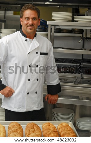 Attractive Caucasian chef standing in a restaurant kitchen with fresh loaves of bread out of focus in the foreground.