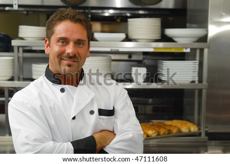 Attractive Caucasian chef standing with arms crossed in a restaurant kitchen. - stock photo