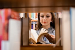 Attractive caucasian girl looking through a book in the bookstore, choosing interesting story to buy