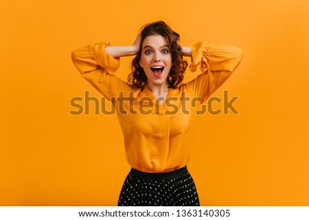 Attractive caucasian girl playing with hair. Studio shot of happy curly woman isolated on yellow background.