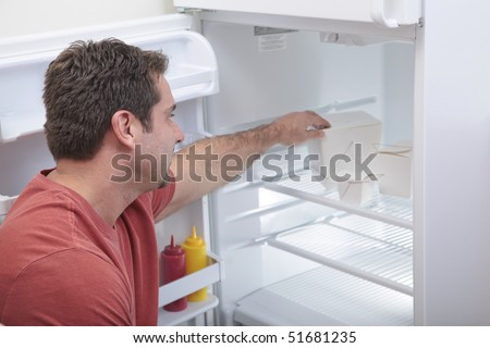 Attractive Caucasian male reaching into a sparse refrigerator