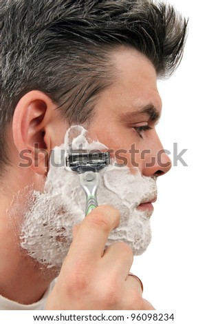 Attractive caucasian mature man shaving in the bathroom at home