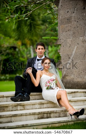 Attractive caucasian newly weds getting married outdoors in a garden