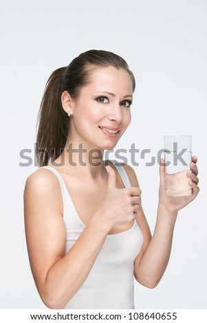 attractive caucasian smiling woman isolated on white studio shot drinking water with thumb-up