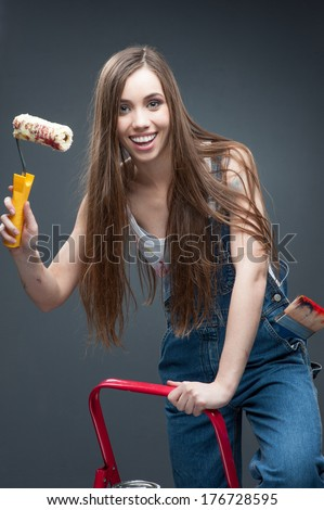 attractive caucasian smiling young woman standing at ladder and holding paint roll