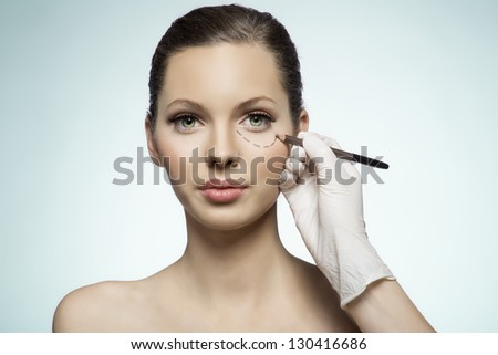 attractive caucasian very young woman whose face is marked with lines for facial cosmetic surgery