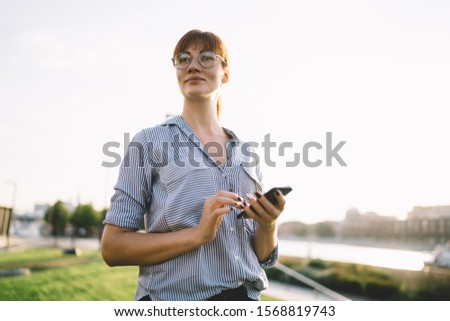 Attractive caucasian woman i n eyewear sending messages via app on mobile phone spending free time in city park, millennial female blogger checking notification on mobile phone outdoors Foto stock ©