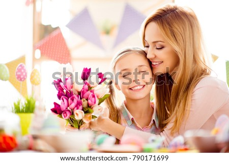 Attractive, charming, pretty, cute, sweet, lovely mother and daugther celebrating Easter, holding bouquet of colorful tulips, enjoying hugging with each other having eyes closed