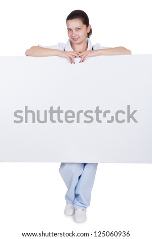Attractive charming young female doctor or nurse with blank white signboard with copyspace peering around the side as she holds it up