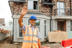 Attractive cheerful friendly worker in vest and hardhat, waving and saying hello looking at camera. builder greeting somebody with raised arm.