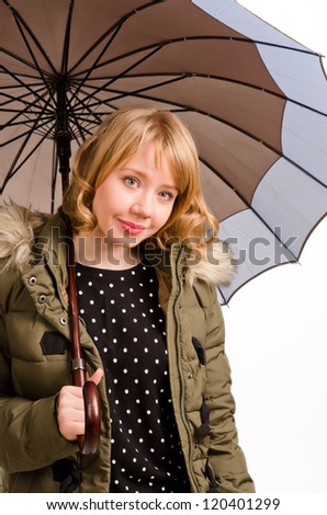 Attractive cheerful young blonde woman with a sweet smile sheltering under a large umbrella in a warm jacket looking at the camera isolated on white