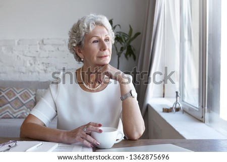 Attractive classy sixty year old mature woman wearing stylish wrist watch and pearl necklace spending nice time at home alone, sitting at her workplace with cup of coffee, looking through window #1362875696