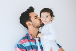 Attractive close up portrait of hipster father kissing his little daughter. Young dad is enjoying time with his child. Handsome father with little girl. Happy father and daughter. Lifestyle family.