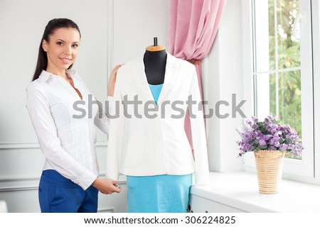 Attractive clothes designer is presenting her new clothing. She is standing near a mannequin and smiling. The woman is looking forward with happiness