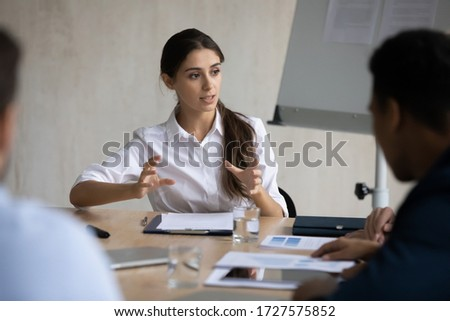 Attractive coach leader businesswoman talking and conducts negotiation in boardroom at meeting. Confidence woman training diverse corporate team at briefing. Young employee share thoughts sit at table