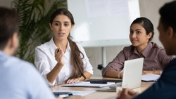 Attractive coach leader businesswoman with indian ethnic partner talking in boardroom at meeting. Confidence woman training diverse corporate team at briefing. Young employee share thoughts sitting.