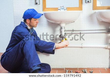 Attractive concentrating plumber repairing sink in public bathroom