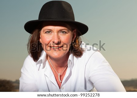 Attractive confident woman wearing a hat middle aged enjoying outdoors. Clear sunny spring day with blue sky.