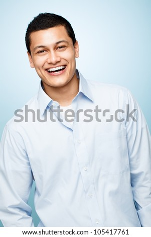 attractive confident young man smiling blue background