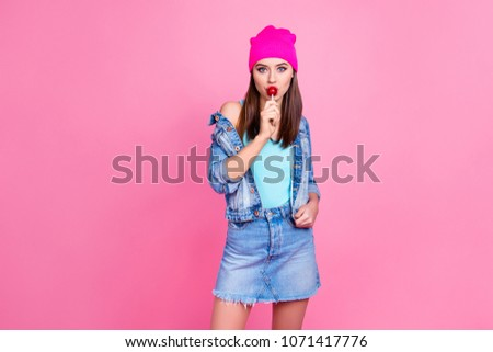 Stock Photo Attractive cool trendy charming girl wearing denim casual shabby ripped jeans shirt jacket pink hat enjoying the taste of lollipop, isolated on pink background, copy-space