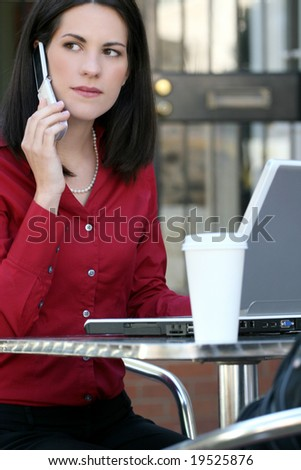 Attractive corporate, business woman working on her laptop outdoors, on cell phone and enjoying a cup of tea, city environment