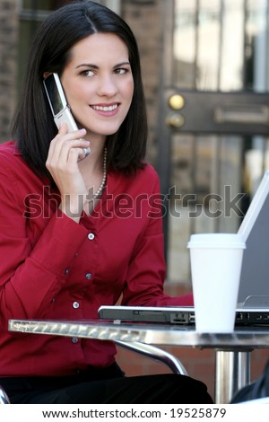 Attractive corporate, business woman working on her laptop outdoors, with a cup of tea, in a city street