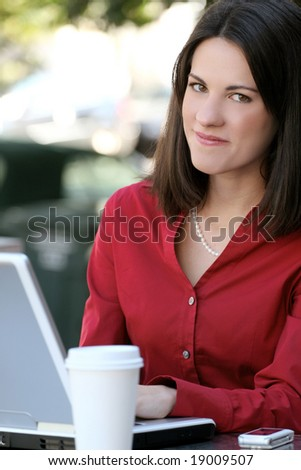 Attractive corporate, business woman working on her laptop with a cup of tea outdoors, in a city street