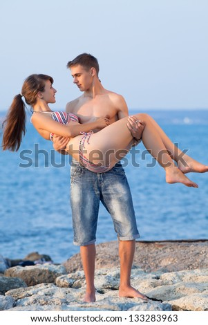 Attractive couple at the sea. Attractive guy and girl are playing at the sea in evening time