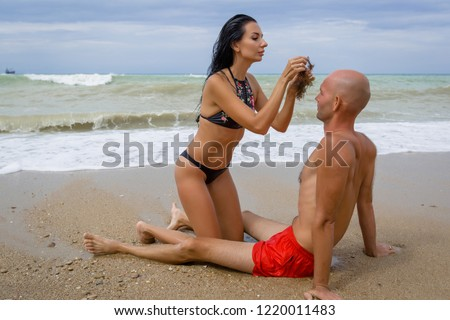 Attractive couple at the sea in summer overcast day. Man and woman in swimwear playing on wet sand in surf line. Female person trying to put seaweed on guy's bald head