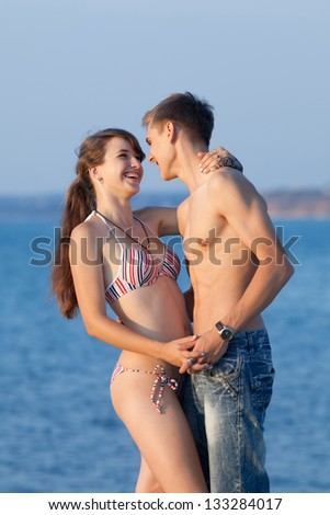 Attractive couple at the sea. Young heterosexual couple flirting at the sea in evening time