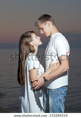 Attractive couple at the sea. Young heterosexual couple flirting on seashore in evening time
