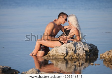 Attractive couple at the sea. Young man and woman in swimwear flirting on wild rock at the sea