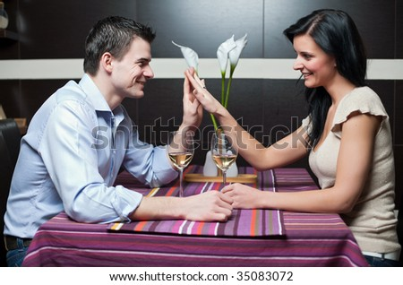 Attractive couple drinking wine and flirting