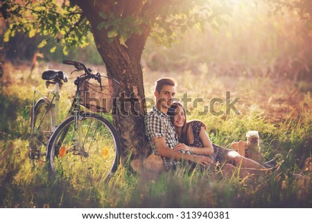 Attractive Couple Enjoying Romantic Sunset Picnic in the Countryside / Vintage style photo with custom white balance, color filters, soft focus effect, and some fine film grain added