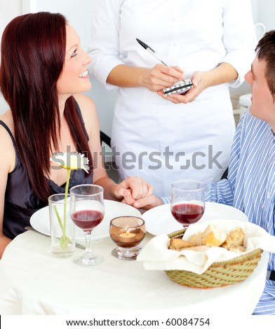 Attractive couple having dinner at the restaurant with waiter taking their order