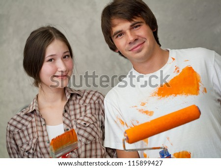 Attractive couple holding brushes