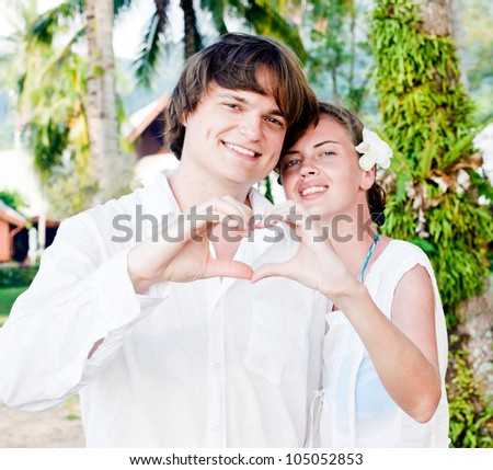 Attractive couple in white showing heart with their hands